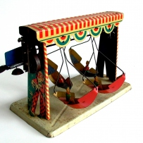 A tin clockwork carnival ride model with boats