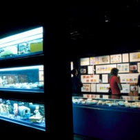 Leunig animated exhibition. A large 3 level display case stands in the foreground. People can be seen looking at drawings in the background.