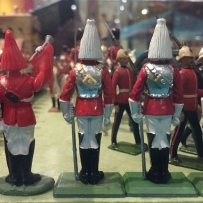This is a photograph of colourful toy soldiers lined up with their backs to the camera