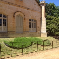 Shot of the Vaucluse House stables and sloping green grass, with raised grass moustache in forground