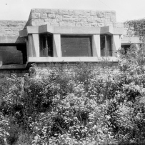 Black and white photo of sandstone house facade with bushes below.