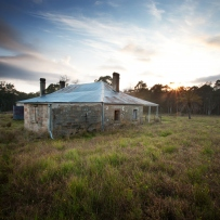 Old farmhouse with atmospheric sky above and trees behind.