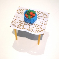 A paper craft fruitbowl on a cardboard, paper and straw craft table.