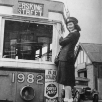 Femal conductor stands on the front of a tram smiling at the camera.