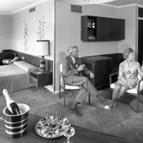 Black and white photograph of men and women sitting in a hotel room.