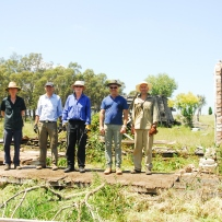 Group of 5 men standing on a section of floor where the Beulah cottage once stood.