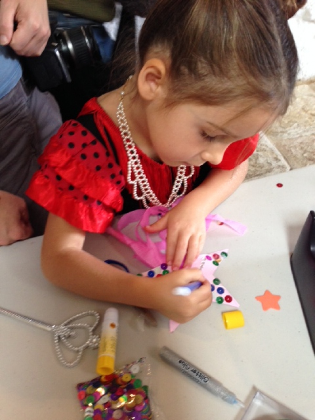 Young girl decorating a fairy wand.