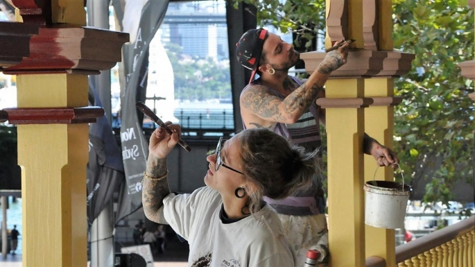 Two people painting wooden verandah posts with street in background.
