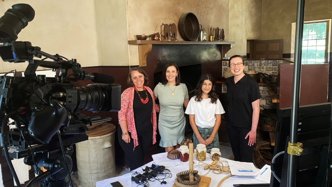 Group of people in colonial era kitchen with camera and recording equipment set up.