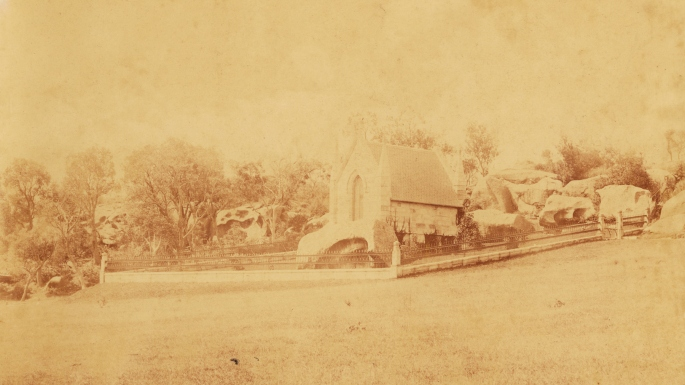Old yellowed image of the mausoleum. It is sitting on top of a large sandstone rock.