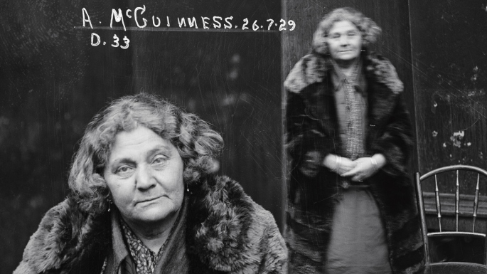 Dual mugshot of woman seated and standing, with standing shot showing blurred movement.