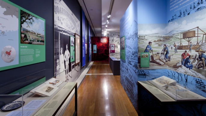 View of exhibition Celestial City with showcases and large wall mounted graphic panels lining either side of a timber floored corridor