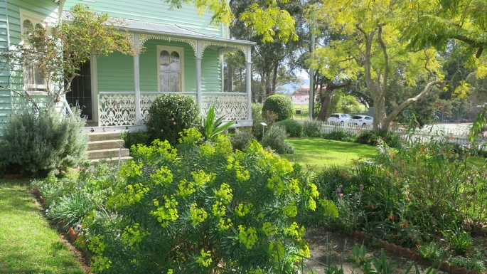 Front verandah of green wooden house with garden wrapping around.
