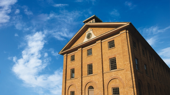 Front of colonial era two storey brick building with blue sky behind.