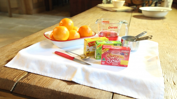 Wooden table with white cloth laid with a bowl of oranges, jelly packets, knives, jugs.