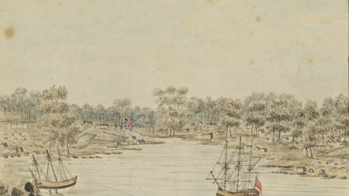 Two ships sit in Sydney Cove. The British flag flies on the shore with several simple buildings in amongst the bush.