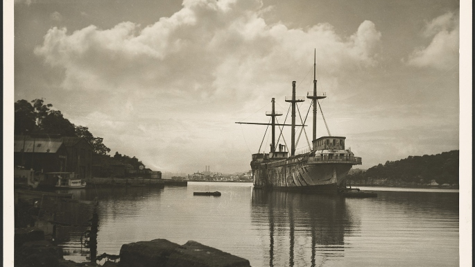 This is a black and white photograph of a three-masted ships with its sails furled moored in a quiet bay