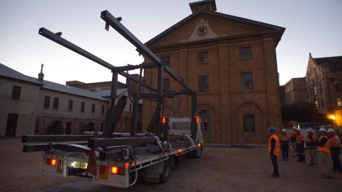 A truck parked out the front of the Hyde Park Baracks with a large metal structure on board.