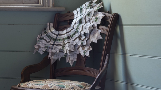 Intricate white paper collar hung over dark wooden chair.
