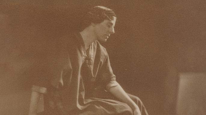 Sepia toned photo of seated woman in profile.