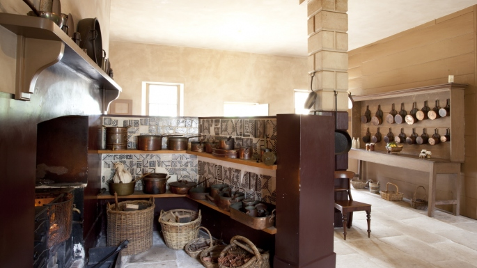 View of colonial kitchen with fireplace and stove enclosed by large masonry screen with pots and pans and utensils on shelves.