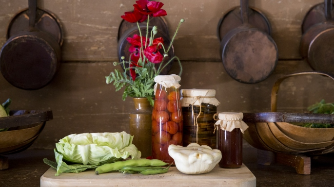 Saucepans hanging on the wall with bottles of preserves, cabbage and flowers on wooden dresser.