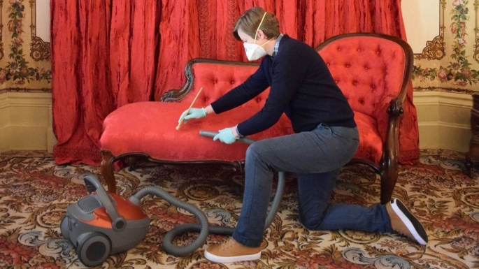 Person kneeling in front of red furniture with vacuum cleaner.