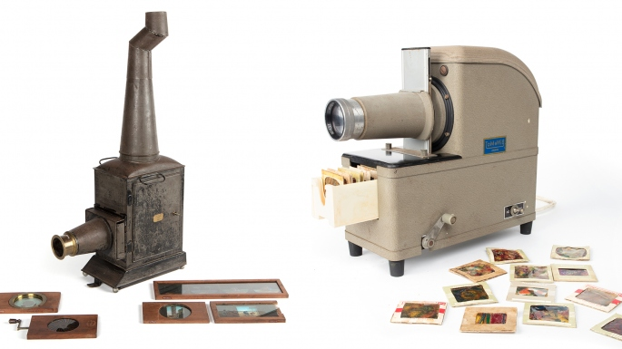 Metal lantern slide projector next to electric projector, both with related slides.