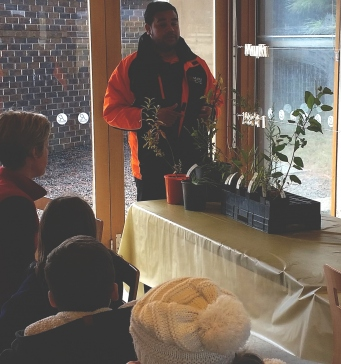 Man presenting a workshop to a group, with potted plants on a table.