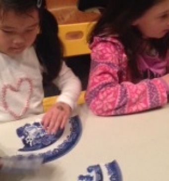 A girl puts the Willow Pattern puzzle together