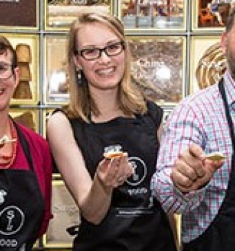 Alysha Buss holding out a piece of cheese at a museum tasting event
