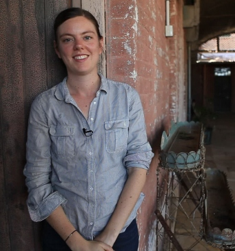 Woman with shirtsleeves rolled up leaning on wall of old shed.