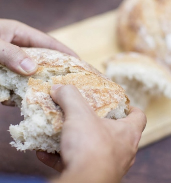 Hands tearing up a loaf of bread