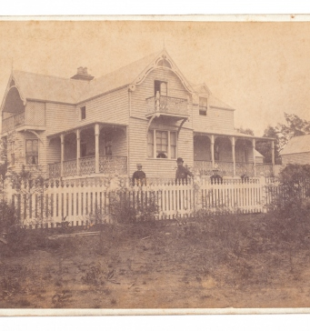 Sepia toned photo of Meroogal house exterior with three figures behind fence.