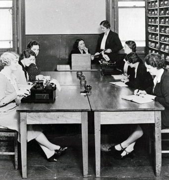 Black and white photo of women dressed in civilian clothing of 1930s, seated around wooden table with typewriters, surrounded by wooden pigeonholes for filing.