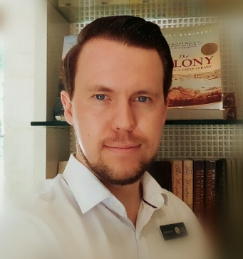 Cameron Allan, A Visitor Interpretation Officer at Sydney Living Museums in his uniform which is a white business shirt and he is in front of a book display at the Vaucluse House Shop