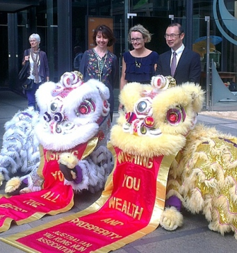 Lion dance costumes with three people standing behind them.
