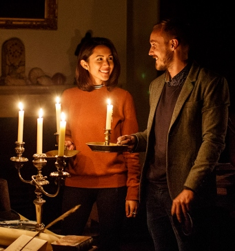 Woman and man standing at fireplace holding candles