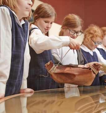 Group of children in school uniform looking at objects on display.