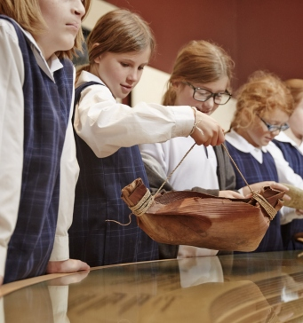 Children in uniform gathered around a glass topped display table.
