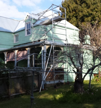 Mint green house with scaffolding and newly installed roofing.