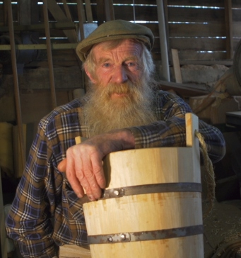 Bearded man in workshop with bucket.