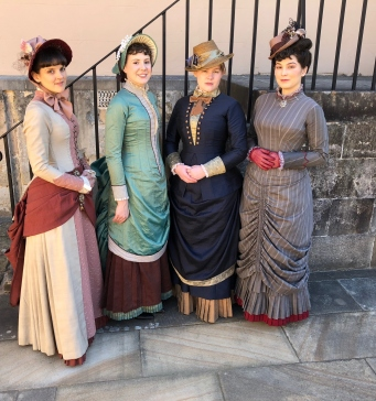 Group of four women in period costumes in front of sandstone steps.