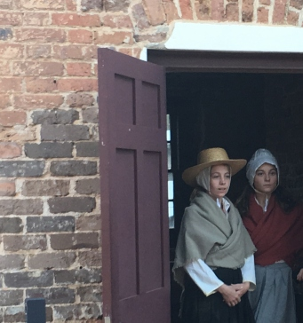 Two actors dressed as convicts in doorway of guardhouse
