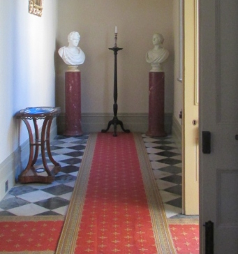 Detail of long hall with furnishings and newly painted walls.
