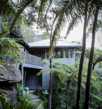 This is a photograph of a timber framed house surrounded by rock walls and tropical style plants