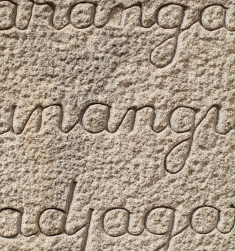 Sandstone carved with words in Aboriginal languages.