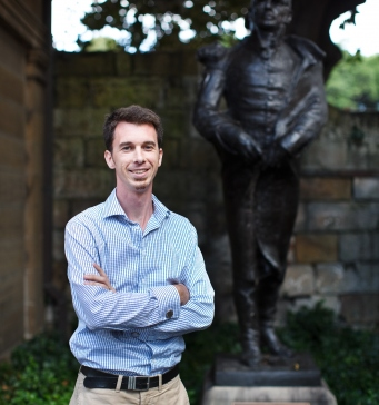This is a colour photograph of a slim man in a blue checked shirt standing in front of a bronze statue