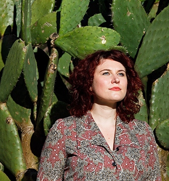 Portrait of woman against background of prickly pear foliage.