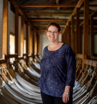 Woman dressed in blue standing in room filled with hammocks.